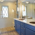 bathroom design with blue vanity cabinet