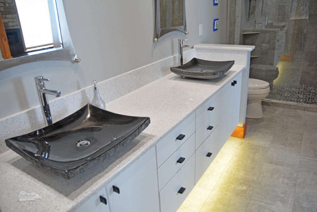 White vanity cabinet with black vessel sinks