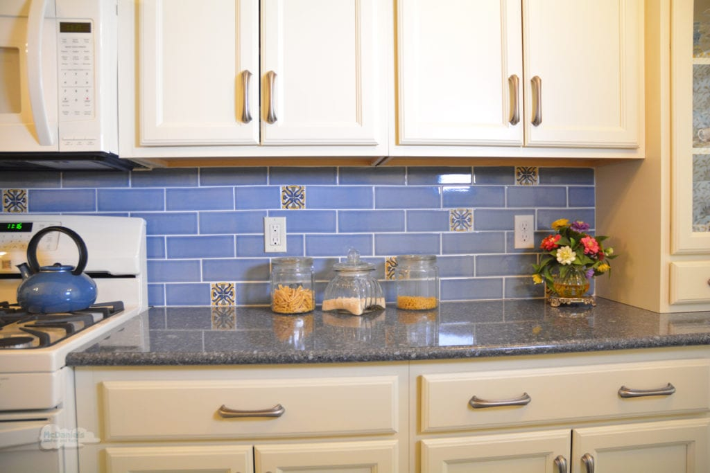 cream cabinets with blue backsplash