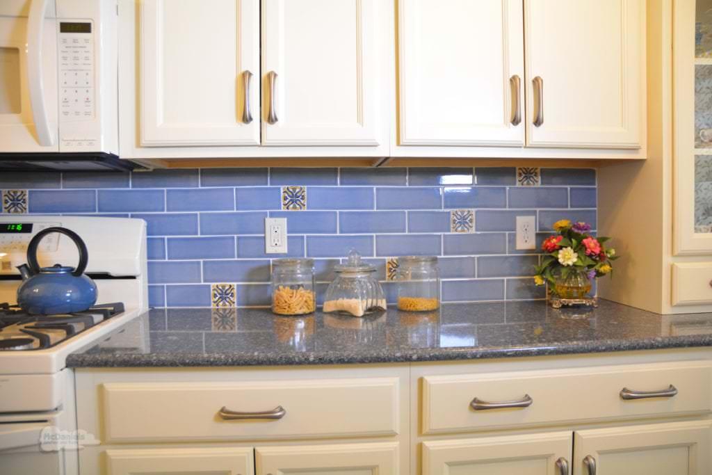 cream cabinets with blue backsplash