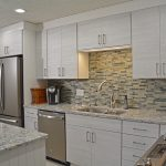 white cabinets with glass tile backsplash