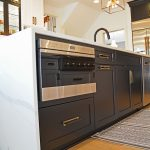 black island cabinets with white waterfall countertop